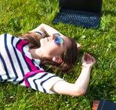 La chica joven se relaja con el ordenador portátil y la taza de café en parque del verano Imágenes de archivo libres de regalías