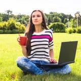 La chica joven se relaja con el ordenador portátil y la taza de café en parque del verano Fotografía de archivo libre de regalías