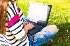 La chica joven se relaja con el ordenador portátil y la taza de café en parque del verano Fotos de archivo