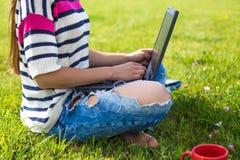 La chica joven se relaja con el ordenador portátil y la taza de café en parque del verano Fotografía de archivo