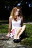 La chica joven se relaja en una piedra en parque Fotografía de archivo