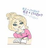 La chica joven se sentó en su escritura del escritorio en un libro Fotografía de archivo libre de regalías