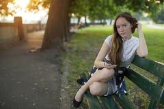 La chica joven se sienta con un smartphone en un banco en parque Fotografía de archivo