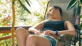 La chica joven se sienta en butaca y la relajación en la terraza de la casa de campo almacen de video