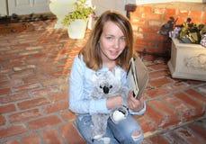 La chica joven se sienta en el pórtico Fotos de archivo libres de regalías