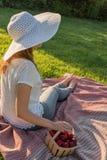 La chica joven se sienta en la hierba Fotografía de archivo libre de regalías