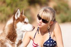 La chica joven se sienta en la playa con el perro Foto de archivo