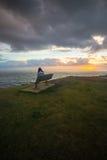 La chica joven se sienta en la salida del sol de observación de la silla Fotografía de archivo