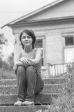 La chica joven se sienta en pasos de progresión Fotos de archivo