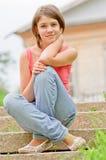 La chica joven se sienta en pasos de progresión Foto de archivo libre de regalías