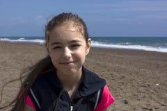 La chica joven se sienta en la playa cerca del mar azul imagen de archivo libre de regalías