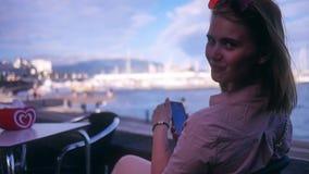 La chica joven se sienta en un café en la playa con un teléfono y una sonrisa linda almacen de video