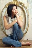 La chica joven se sienta en un suelo Fotografía de archivo libre de regalías