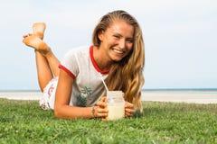 La chica joven se sienta en una hierba en el país tropical de la isla Samui, el smoothie de las bebidas de la muchacha Imagen de archivo libre de regalías