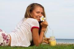 La chica joven se sienta en una hierba en el país tropical de la isla Samui, el smoothie de las bebidas de la muchacha Fotos de archivo