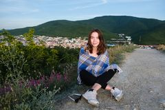 La chica joven se sienta en una montaña con la opinión de la ciudad, envuelta en una manta Tarde fresca del verano Imagenes de archivo