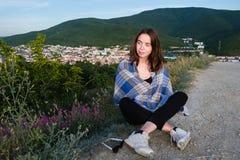 La chica joven se sienta en una montaña, envuelta en una manta Tarde fresca del verano en las montañas Fotografía de archivo libre de regalías
