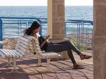 La chica joven se sienta en una puesta del sol en la playa, y escribió un mensaje encendido Imágenes de archivo libres de regalías