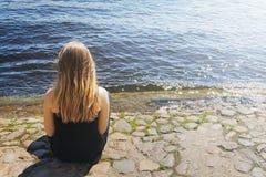 La chica joven se sienta por el agua Imagenes de archivo