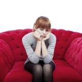 La chica joven se sienta solamente en el sofá rojo Foto de archivo libre de regalías