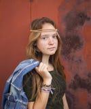 La chica joven se vistió en estilo del hippie, contra un fondo de la pared del metal de Borgoña Imagen de archivo libre de regalías