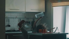 La chica joven soñolienta torpe vierte el jugo en el vidrio rojo, resbalones y caída encima metrajes