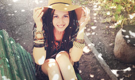 La chica joven sonriente bonita con los dreadlocks se vistió en el estilo del boho, reclinación al aire libre Imagen de archivo