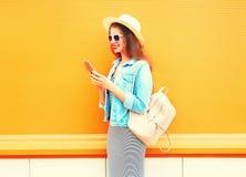 La chica joven sonriente de la moda está utilizando el smartphone en la ciudad Imagen de archivo