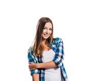La chica joven sonriente en azul comprobó la camisa, aislada Fotografía de archivo