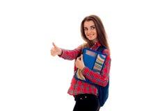 La chica joven sonriente en camisa da la clase y guarda la carpeta con los cuadernos Imagen de archivo