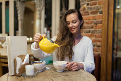 La chica joven sonriente en el restaurante vierte té verde de la tetera amarilla en una taza Foco en una taza de té imagen de archivo