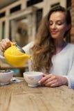 La chica joven sonriente en el restaurante vierte té verde de la tetera amarilla en una taza Foco en una taza de té fotografía de archivo