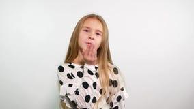 La chica joven sonriente en el top blanco con los puntos negros envía beso del aire en la cámara almacen de metraje de vídeo