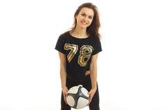 La chica joven sonriente en traje negro mira al lado y a sostener un balón de fútbol Imagenes de archivo