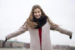 La chica joven sonriente en una capa se separó los brazos Muchacha en una capa negra, una bufanda y un vestido rojo contra un cie Fotografía de archivo libre de regalías