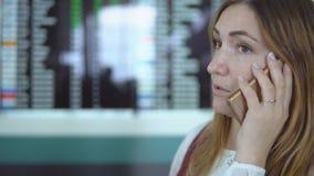 La chica joven sonriente habla en smartphone en el fondo del marcador borroso con el aviso almacen de metraje de vídeo