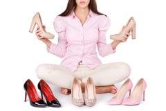 La chica joven sonriente presenta cuatro pares modernos de zapatos de tacón alto aislados en un fondo blanco imagen de archivo