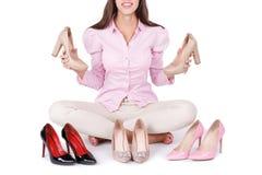 La chica joven sonriente presenta cuatro pares modernos de zapatos de tacón alto en un fondo blanco fotografía de archivo