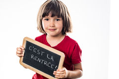 La chica joven sonriente que lleva a cabo la escritura slate para fresco de nuevo a escuela Fotos de archivo libres de regalías