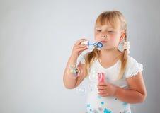 La chica joven sopla hacia fuera burbujas de jabón Imagenes de archivo