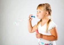La chica joven sopla hacia fuera burbujas de jabón Fotografía de archivo