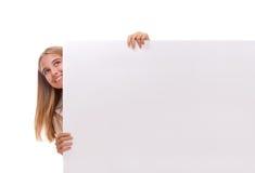 La chica joven sorprendente feliz está haciendo estallar hacia fuera del lado de la bandera en blanco blanca, aislado Imagenes de archivo
