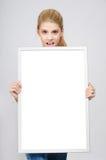 La chica joven sorprendió llevar a cabo en frente a un tablero en blanco blanco. Imagenes de archivo