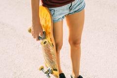 La chica joven sostiene un monopatín en su mano, pantalones cortos y un top sin mangas imagen de archivo libre de regalías