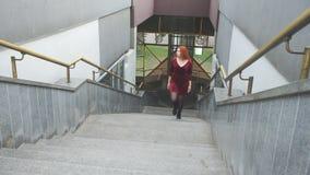 La chica joven sube las escaleras almacen de metraje de vídeo