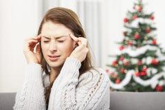La chica joven tiene dolor de cabeza de la tensión de la Navidad Imágenes de archivo libres de regalías