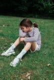 La chica joven tiene un resto en la hierba del parque imagen de archivo