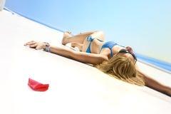 La chica joven toma el sol en un yate en el sol del verano Imagen de archivo libre de regalías