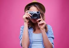 La chica joven toma una foto con una cámara de plata retra Fotos de archivo