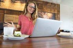 La chica joven trabaja en el ordenador y la torta, comida en el ordenador, un mún hábito come foto de archivo libre de regalías